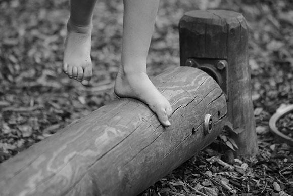 Heilpädagogik barfuß Balancieren auf einem Holzbalken